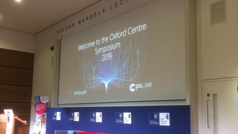 "A photo of the stage set for the CRUK Oxford Centre symposium with the slide reading ""Welcome to the Oxford Centre Symsposium 2019"""