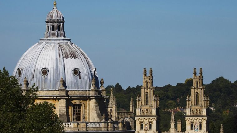 A photo of the Oxford skyline against a blue sky, featuring the Radcliffe Camera and other surrounding buildings.