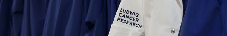 A photo of blue and white Ludwig Cancer Research lab coats hanging on hooks