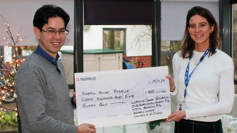 A photo of a cheque presentation ceremony of £750 to Sobell House with Stan Ng and a member of Sobell House posing in front of a Christmas tree decorated with fairy lights