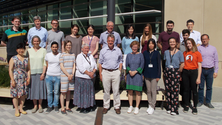 A photo of Professor Sir Peter Ratcliffe with the members of his research group, posing outside the NDM Research Building on a sunny day