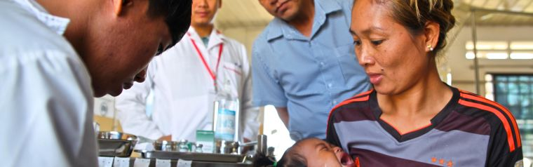 Health care worker treating a baby