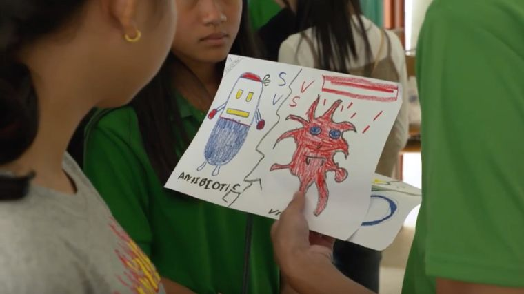 Woman being shown drawing of an antibiotic and a virus