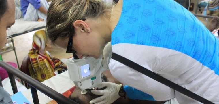 Katherine Plewes examines a severe malaria patient in Bangladesh