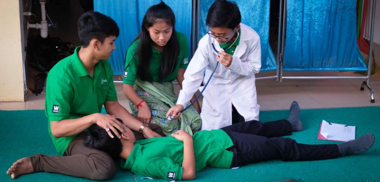 Health care worker using a stethoscope on a patient