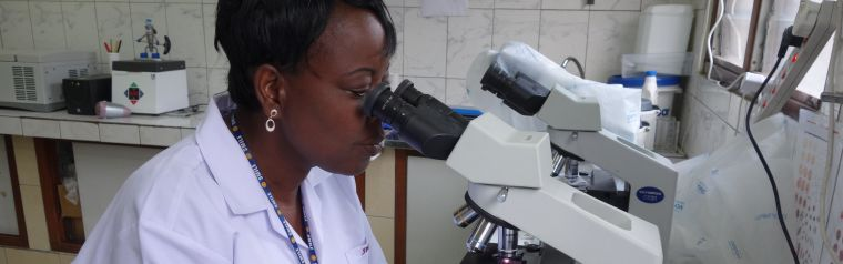 Scientist operating a microscope