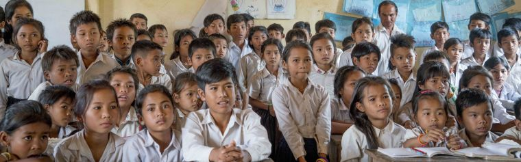 A large group of Cambodian school children looking intently whilst being educated on the prevention of malaria.