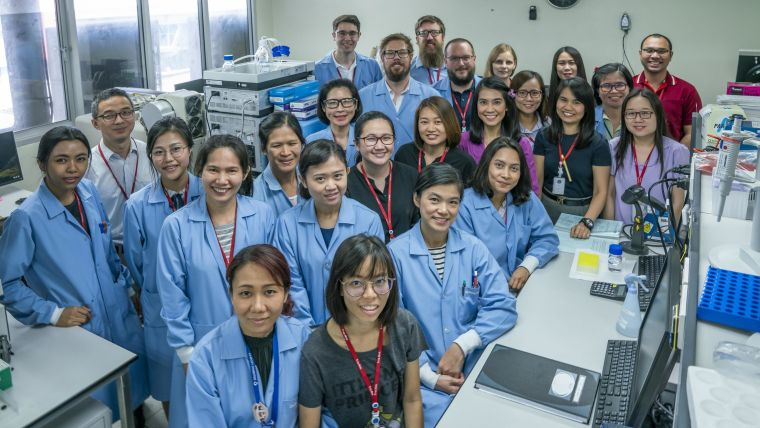 Group picture of the Clinical Pharmacology. They are in a lab and all wearing blue lab coats