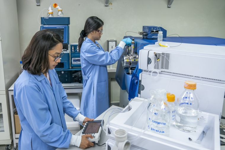 Two scientist, Dr Phornpimon Tipthara Wong and Senior Analyst Siribha Apinan wearing lab coats and operating the high-resolution Triple-TOF LC-MS system.