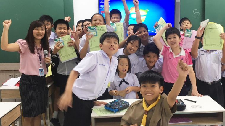 Group of Thai primary age students in a classroom, all smiling and very enthusiastically putting their  fists in the air