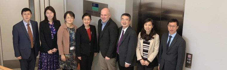 Members from COI and the Ministry of Science standing in the COI office corridor