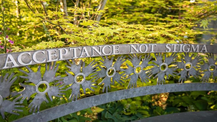 """Image of a garden with a signpost reading """"Acceptance of Stigma"""""""