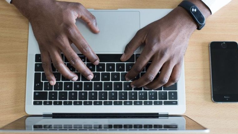 Hands resting on a laptop keyboard