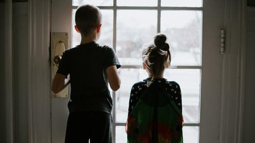 A taller boy and a girl with their backs turned looking out a glass paned door.