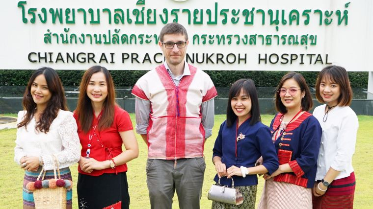 Chiangrai Clinical Research Unit Team, with from left to right: Nipaphan Kanthawang (Bee), Nidanuch Tasak (Pui), Carlo Perrone, Nongyao Khatta (Ann), Ploypatcha Kaewwiset (Maew), Areerat Thaiprakong (Zulin). They stand in front of a banner that says Chiangrai Prachanukroh Hospital (in Thai as well, first row) and Office of the permanent Secretary of Public Health (second row); Chiangrai Prachanukroh Hospital (third row)