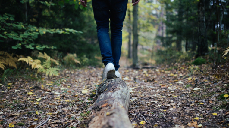 Woman walking away across a log in the forest