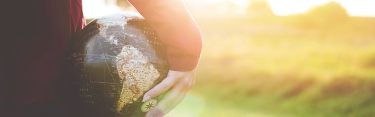 A cropped person holding a globe looking into the sun