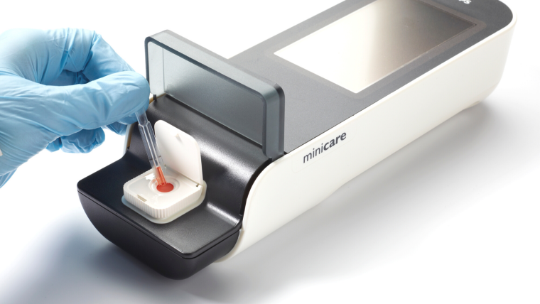Small handheld machine with a woman dropping blood into it to test for cancer