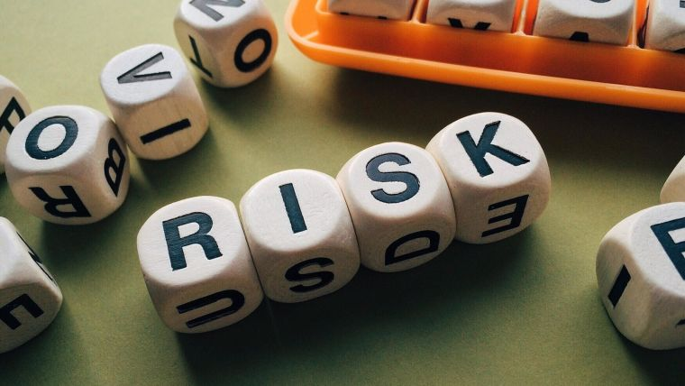 Wooden blocks spelling out 'RISK'