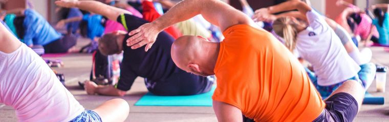 People sat on mats stretching during a yoga class