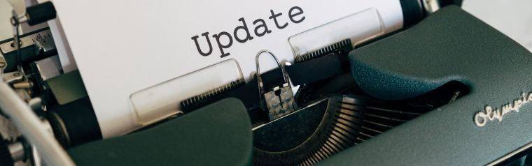 Photo of a typewriting machine with a paper with typed text 'Update'.
