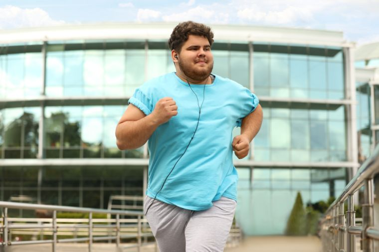 A young man running outdoors.