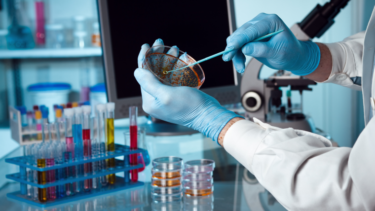 A scientist holding a petri dish in the lab with a monitor and microscope in the background.