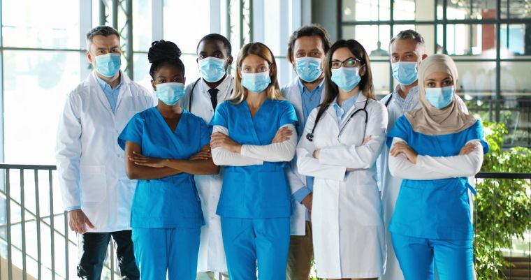 Group of doctors and nurses standing together wearing face masks