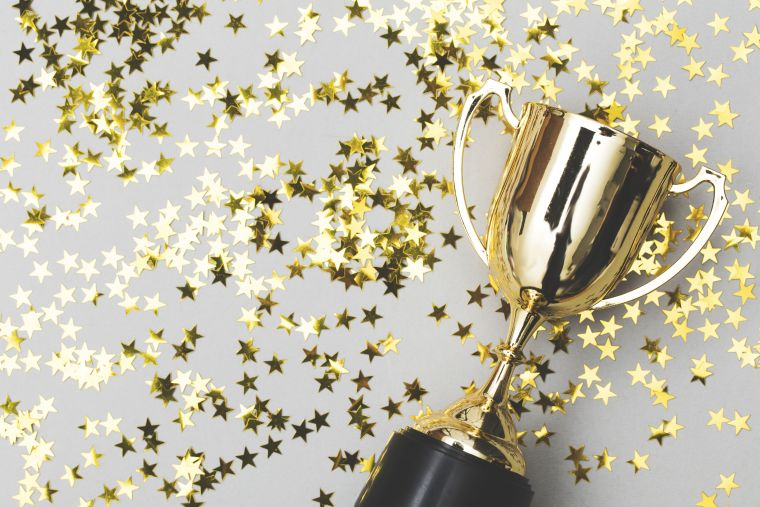An image of a golden trophy scattered with stars