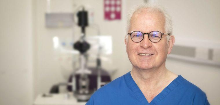 Peter Scanlon smiling while wearing scrubs