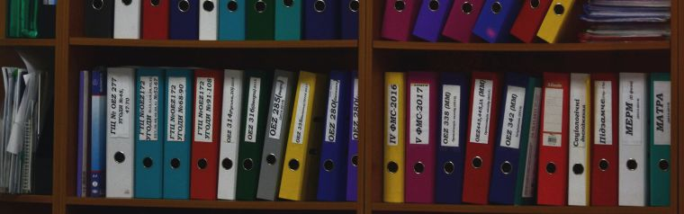 photo of  a shelf with many files with documents