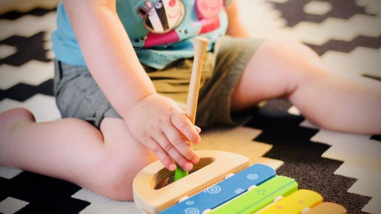Young child sitting on the floor next to a xylophone