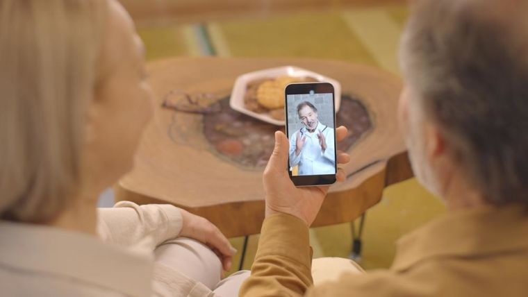 Image of two older people talking to a doctor on their mobile phone