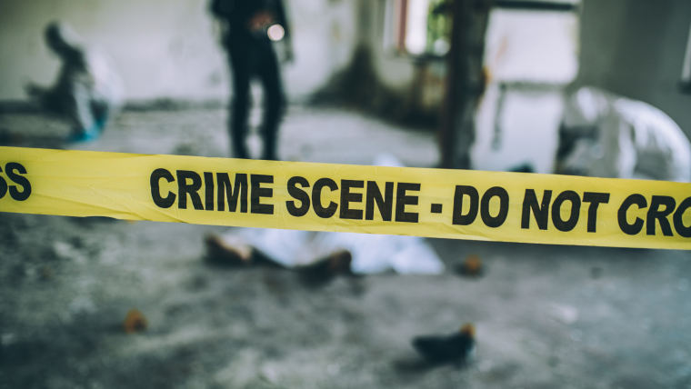 Image shows police tape marking the boundary of a crime scene. The tape reads: crime scene, do not cross.