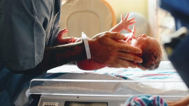 Photo of newborn baby being weighed