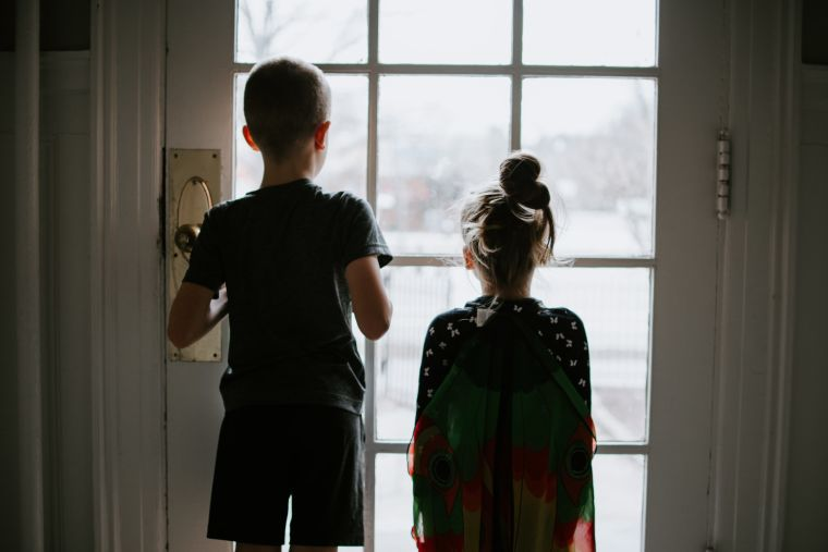 Kids looking outside at the world. Stuck inside during a pandemic quarantine.