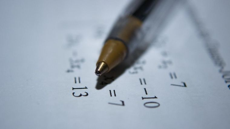 Biro on top of white paper with maths equations