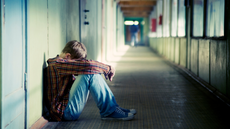 Teenager curled up in a ball leaning against lockers in a school with their head in their arms.