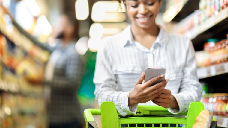 A woman using her phone while food shopping