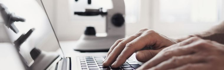 Researcher using laptop with microscope in the background