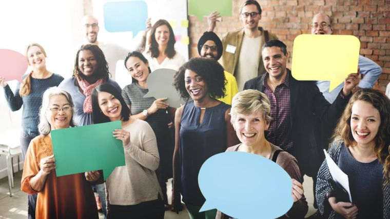 A group of people holding paper speech bubbles.