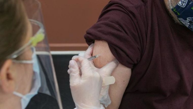 Healthcare worker administering a vaccine to a patient