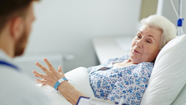 Cancer patient in a bed talking to a nurse