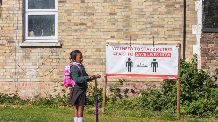 Royalty-free stock photo ID: 1768945394. London, UK - 16 June, 2020 - Social distancing sign with an indication of 2 metres distance in a park and a girl riding a scooter through