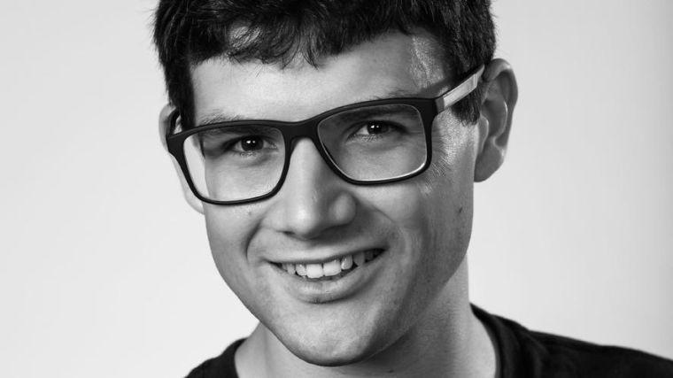 Headshot of Alexander, male smiling at camera wearing glasses