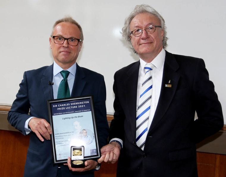 Professor David Paterson presents the Sherrington Prize Lecture speaker Professor Gero Miesenböck with a framed poster of the Lecture and the Sherrington Prize Medal.