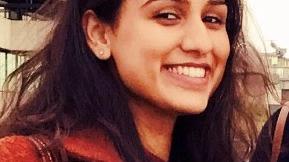 Headshot of Priyanka, female smiling at camera wearing red jacket