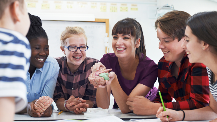 Young people sat in class holding the model of the brain, talking and smiling.