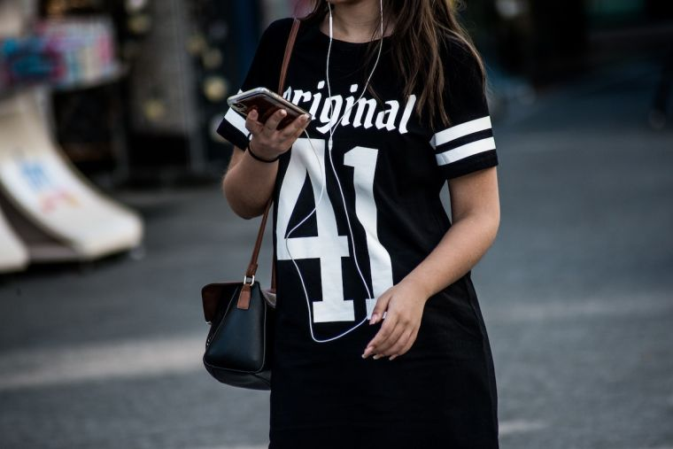 Girl wearing black sports shirt looking at mobile phone.