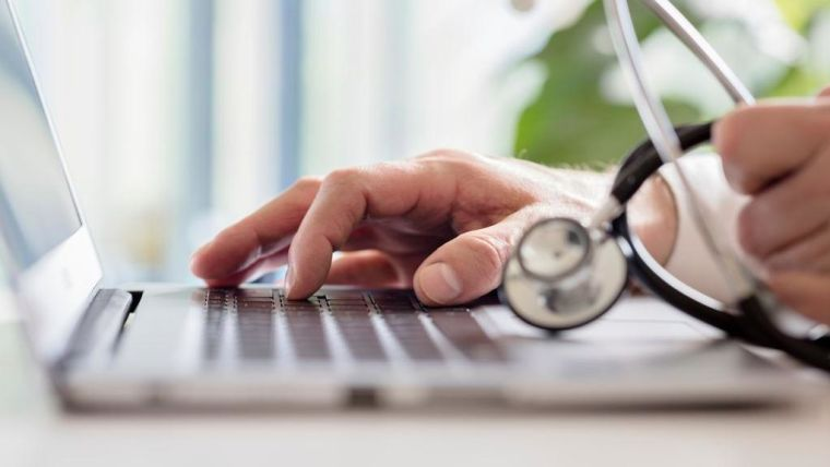 Healthcare professional looking at a laptop with stethoscope in hand